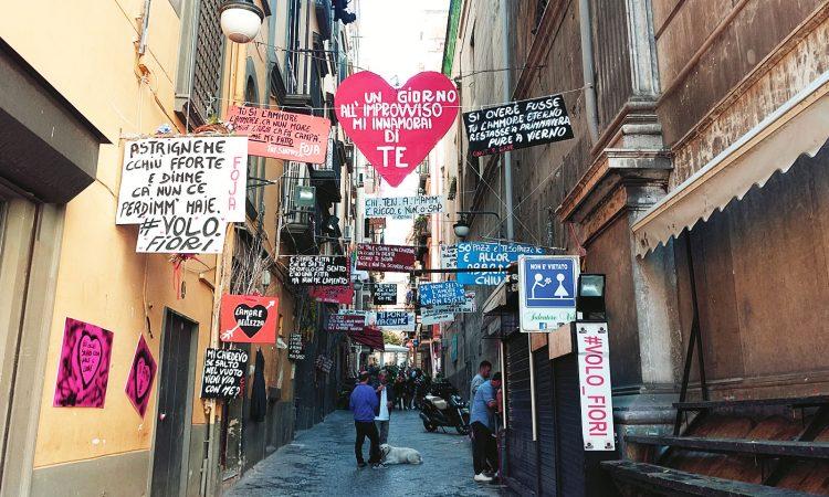 Kleine Gasse im spanischen Viertel mit Schildern und Hund am Wochenende in Neapel