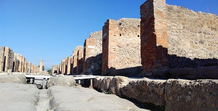 Straße in Pompeji gesäumt von Wänden und Ruinen