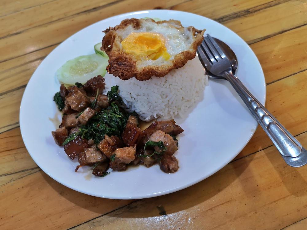 Thailändisches Streetfood: Basil Pan Fried Pork mit Ei/Egg auf Reis. Wanderhunger