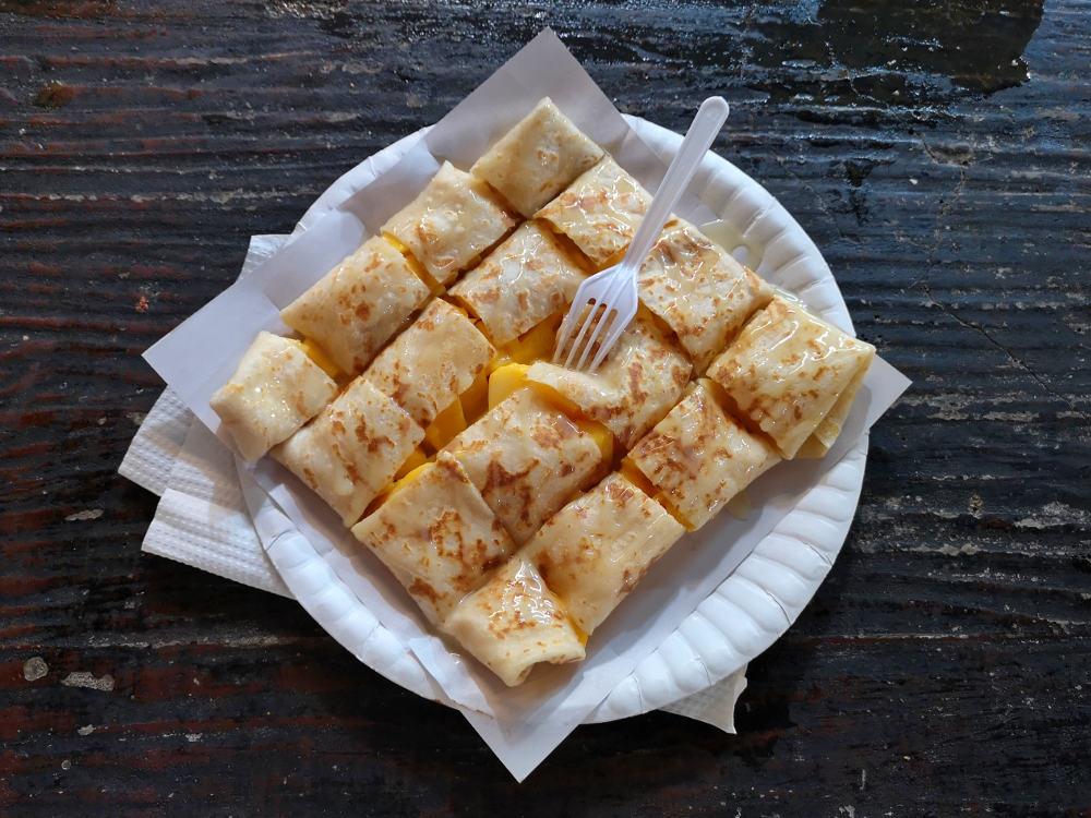 Eine typische Süßspeise in Thailand ist ein Pancake oder ein Crepe gefüllt mit vollreifem Obst, wie hier Mango. Wanderhunger