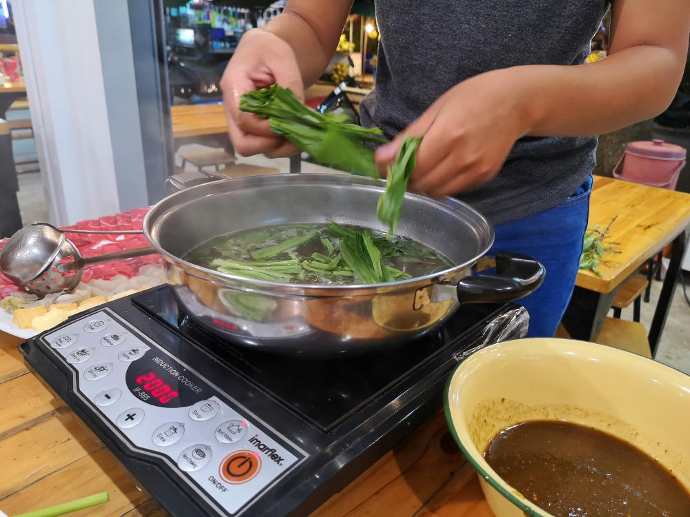 Kräuter wie Thai-Basilikum kommen zuerst in die Suppe des Thai Hotpots. Wanderhunger