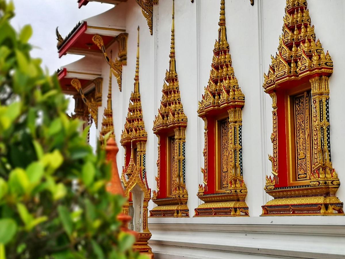 Reich verzierte Fensterrahmen am Haupttempel des Wat Chalong Tempels auf Phuket. Wanderhunger