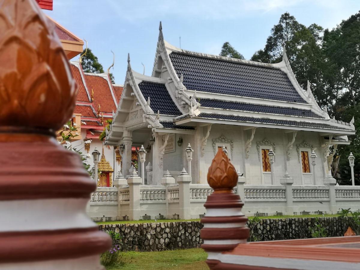 Ein wunderschönes weißes Tempelgebäude im Tempel Wat Kathu auf Phuket. Wanderhunger