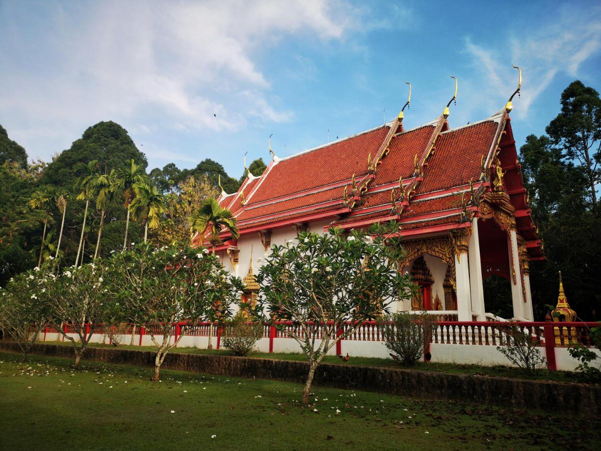 Tempelgebäude in der Tempelanlage von Wat Kathu auf Phuket. Umgeben von Frangipanibäumen. Wanderhunger