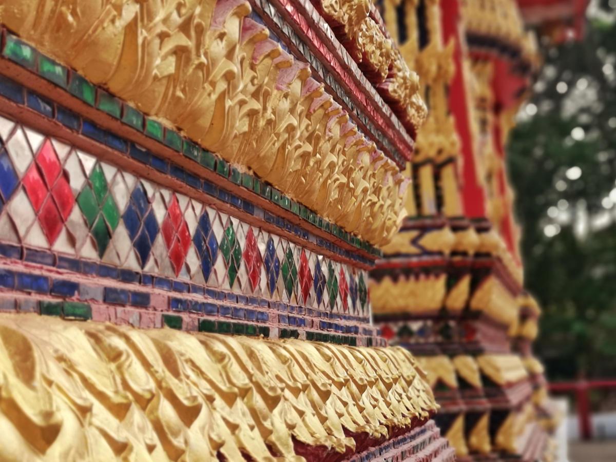 Goldene Details an einem der Tempelgebäude im Tempel Wat Kathu auf Phuket. Wanderhunger