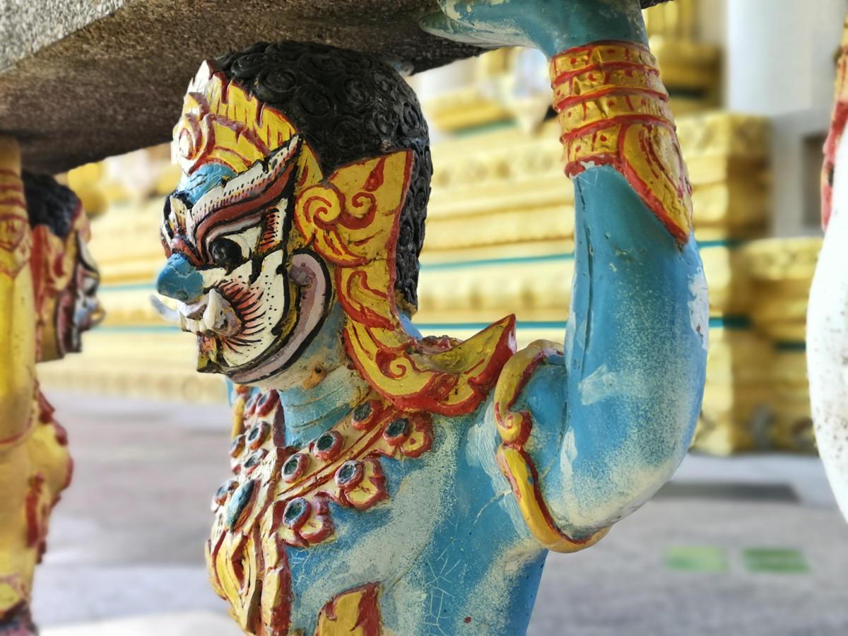 Reichverzierte Atlas-Figuren aus Holz zieren die Geländer rund um den Haupttempel von Wat Khao Rang auf Phuket. Wanderhunger