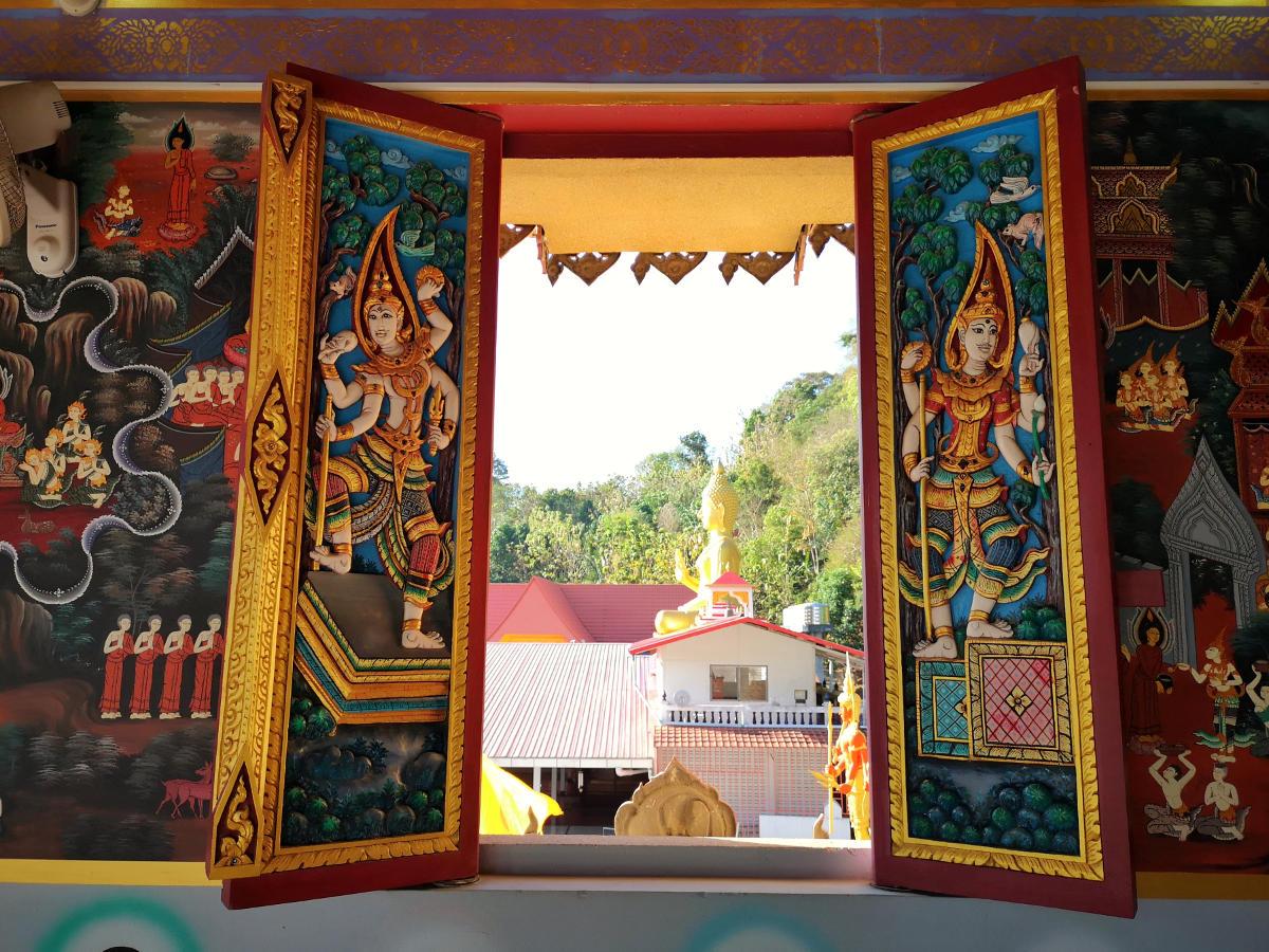 Reichverzierte Fensterläden im Haupttempel von der Tempelanlage Wat Khao Rang in Phuket mit Blick auf den goldenen Buddha. Wanderhunger