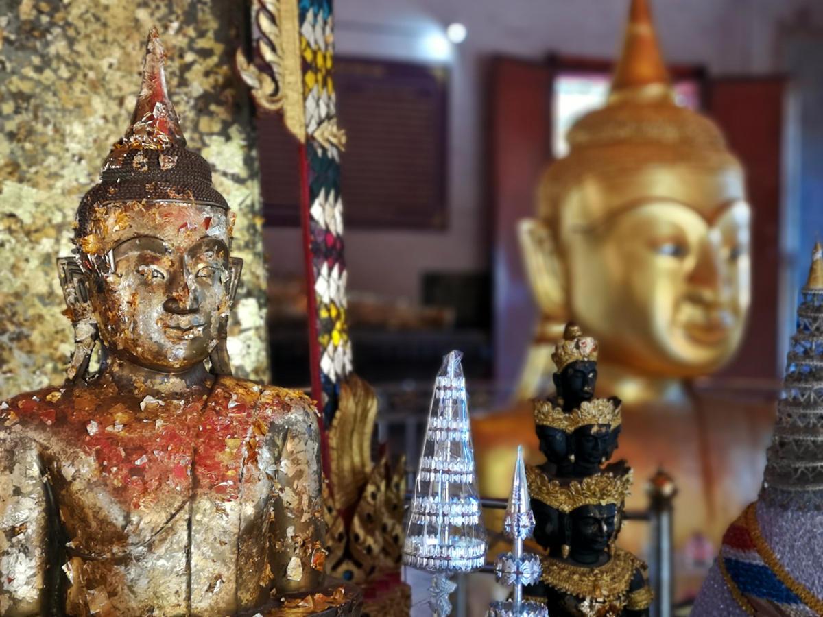 Gläubige verzieren die Statuen im Inneren des Haupttempels von Wat Phra Tong auf Phuket mit Blattgold als Opfergabe. Wanderhunger