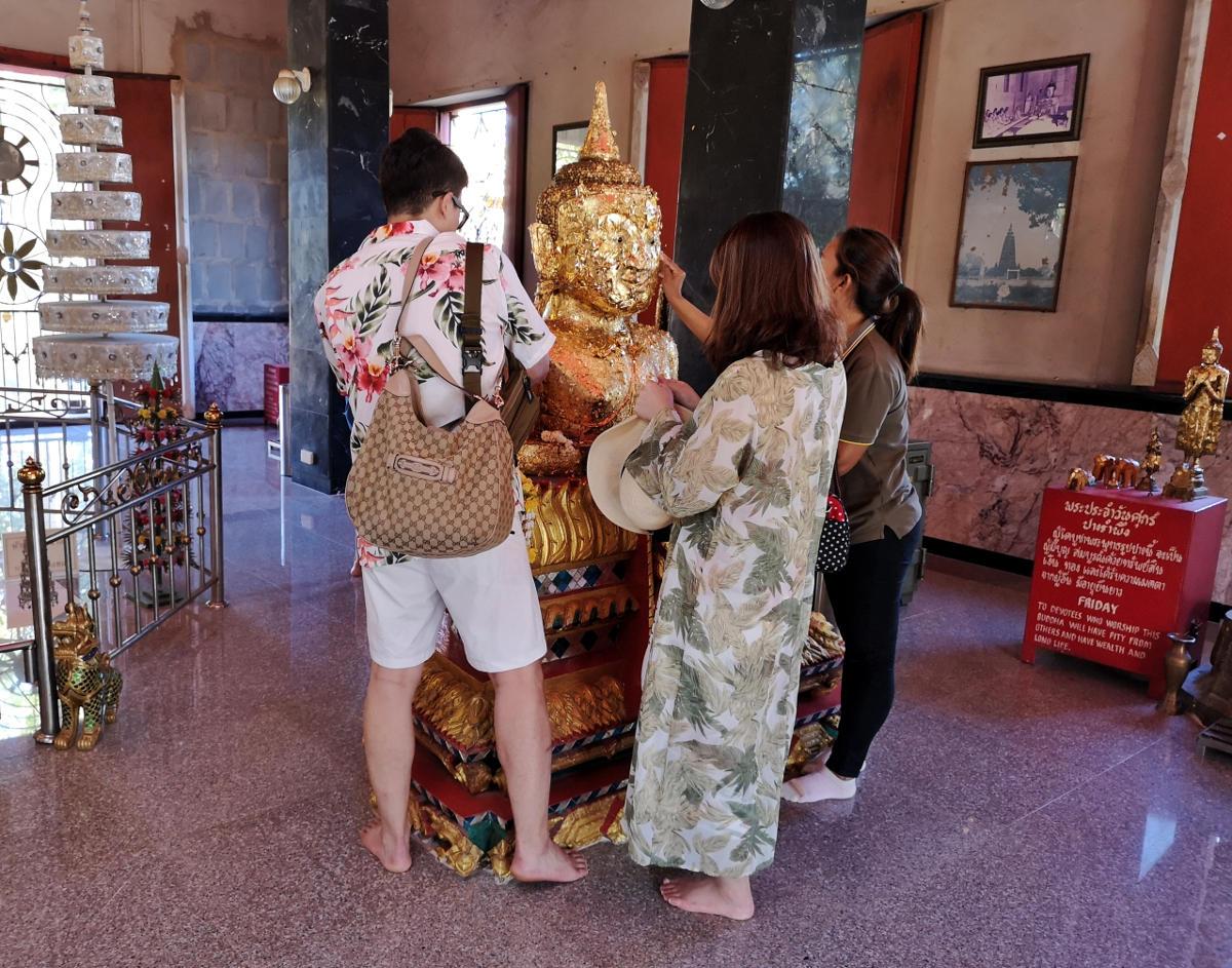Gläubuge verzieren die Statuen mit Blattgold als Opfergabe an den Tempel. Wanderhunger