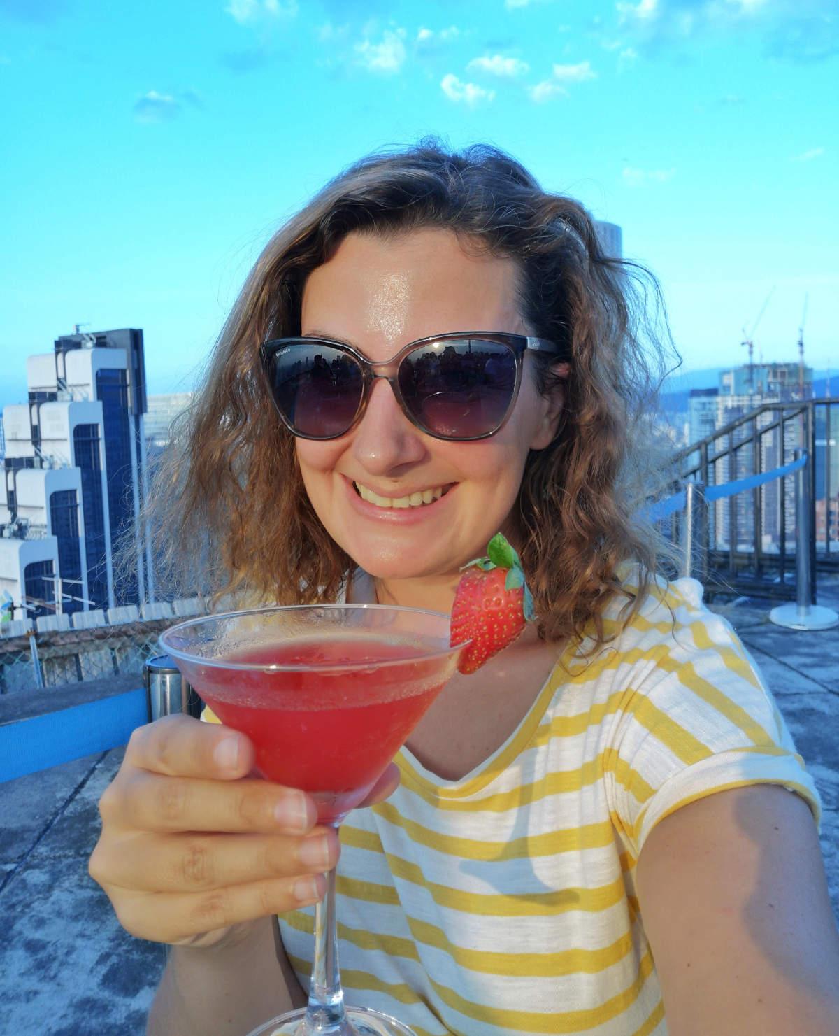 Ich genieße eine Strawberry Margarita zum Happy Hour Preis auf der Heli Lounge Bar in Kuala Lumpur, einer Cocktailbar auf einem Helikopter Landeplatz. Wanderhunger