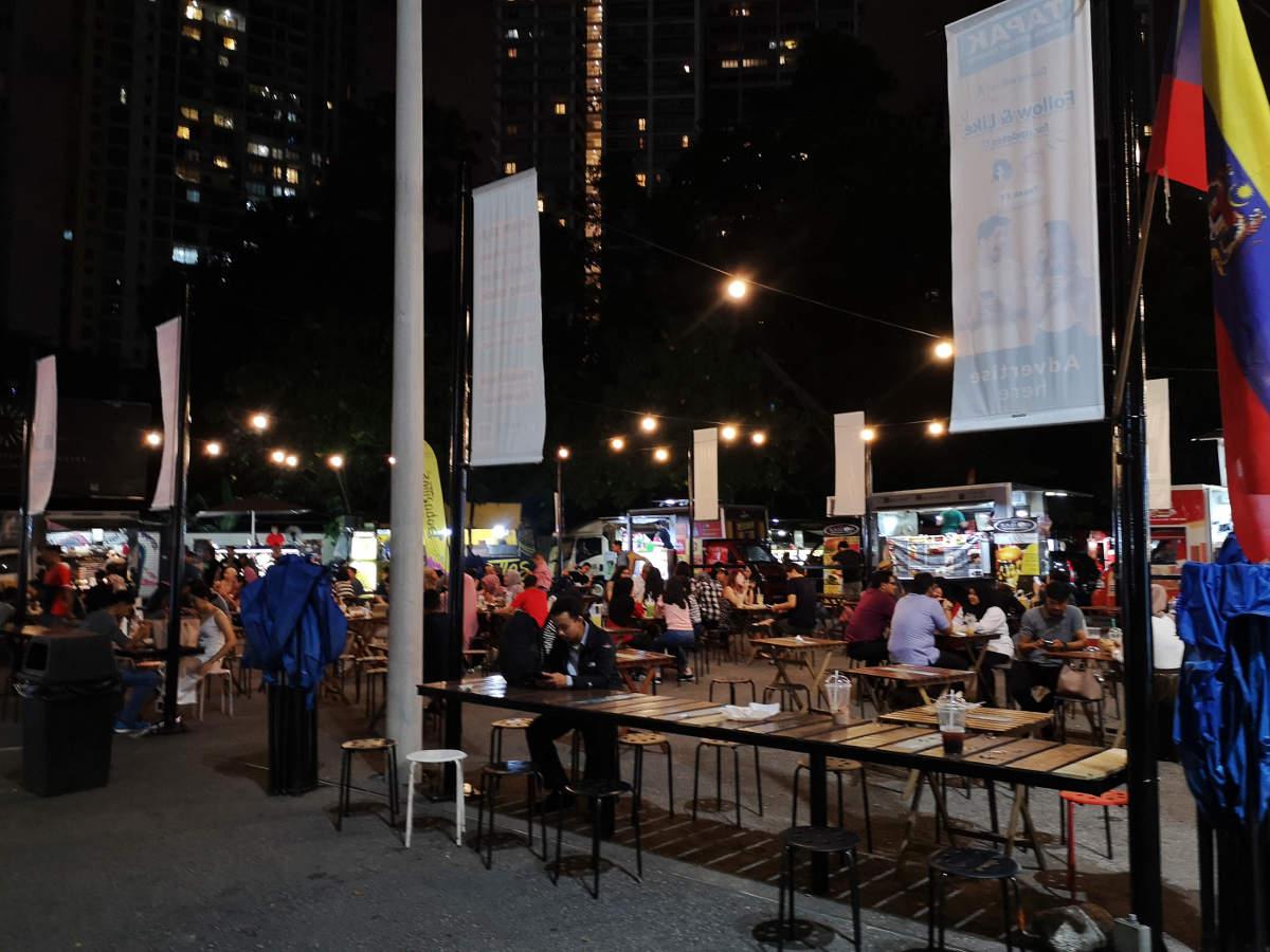 Außen herum stehen die Foodtrucks im Kreis, innen eine große Anzahl an Tischen und Stühlen, wo man bequem essen und trinken kann. Tapak Street Food Market in Kuala Lumpur KLCC. Wanderhunger