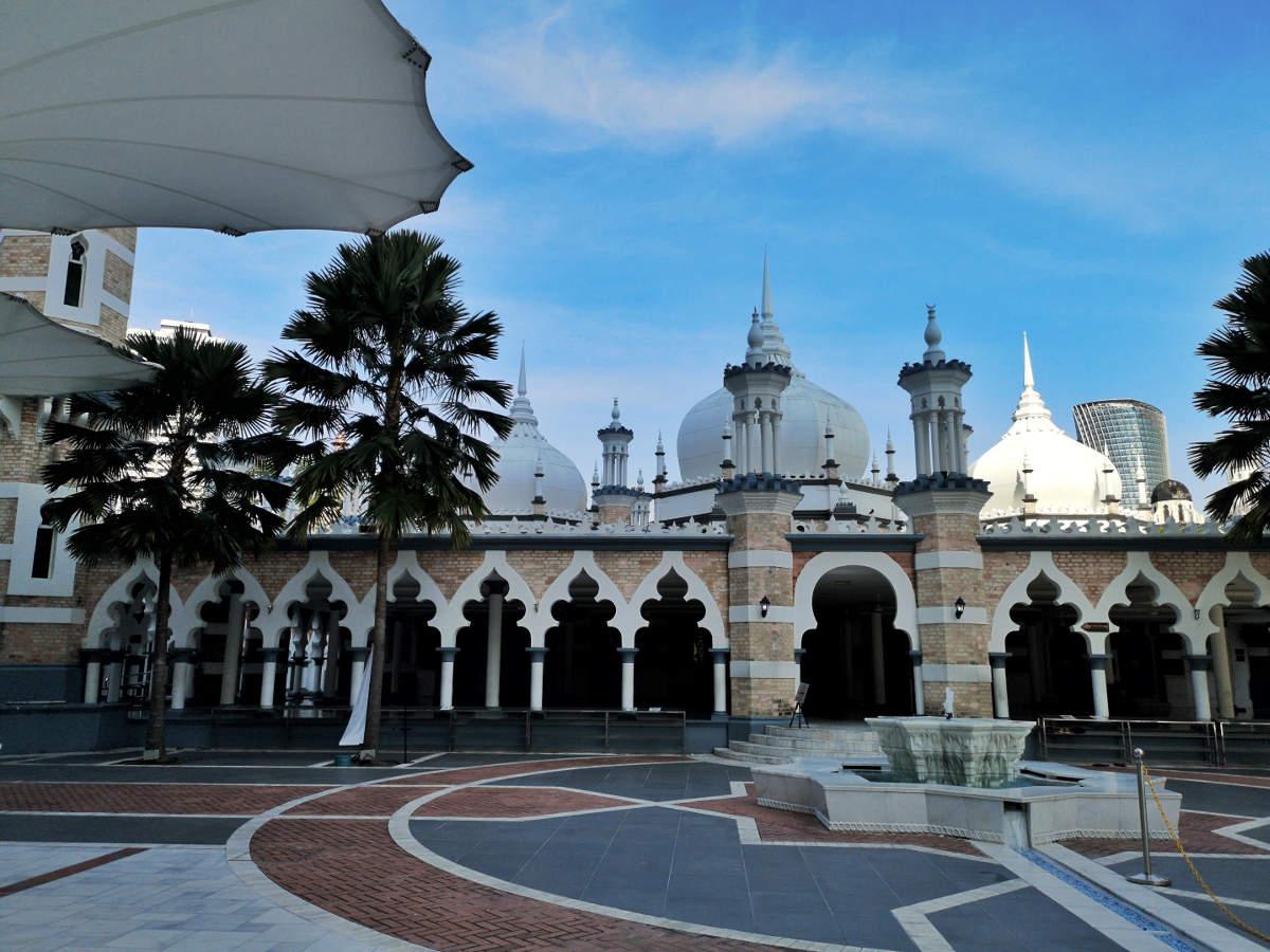 Die Seitenansicht der Masjid Jamek Moschee mit einem schönen sternförmigen Brunnen davor. Wanderhunger