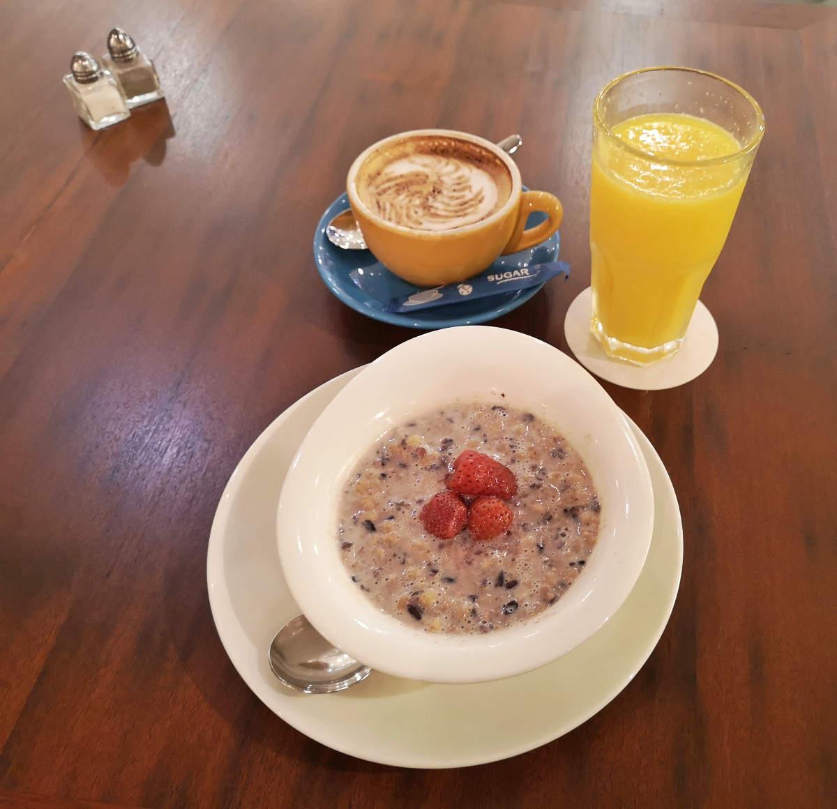 Frühstück und Shopping verbindet sich am besten im Nutmeg Cafe in Kuala Lumpur Bangsar Village, hier mit Porrige, Cappuccino und Orangensaft. Wanderhunger