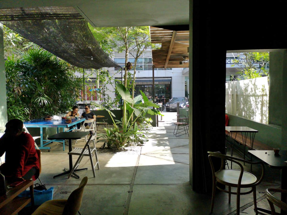 Der Eingang und Garten mit Sitzplätzen des Feeka Coffee Roasters in Kuala Lumpur. Wanderhunger